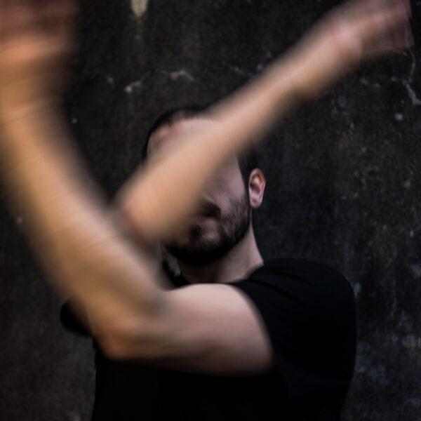 Danser Wannes Labath met armen in beweging en die elkaar kruisen voor het aangezicht. Promobeeld voor de voorstelling BY FOR WITH WANNES, genomen door fotograaf Jan Fedinger in het Franse Orléans.