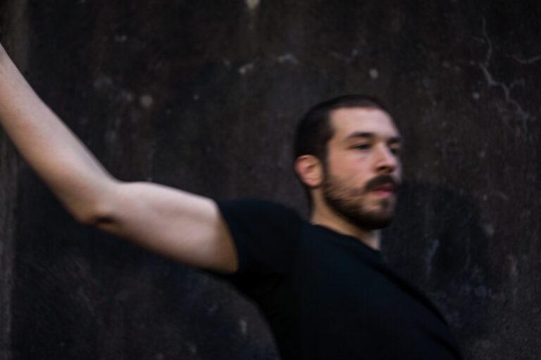 Danser Wannes Labath in volle beweging, het aangezicht naar linke gekeerd en de rechterarm die gestrekt volgt, achter het lijf. Promobeeld voor de voorstelling BY FOR WITH WANNES, genomen door fotograaf Jan Fedinger in het Franse Orléans.